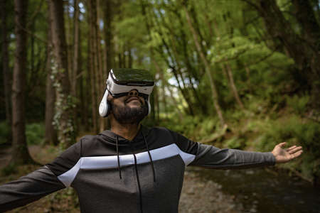Young man wearing vr glasses while standing with arms outstretched amidst trees in forest
