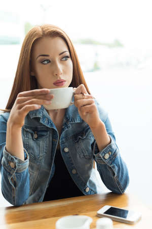 contemplated: Thoughtful young woman holding coffee cup by window in cafe