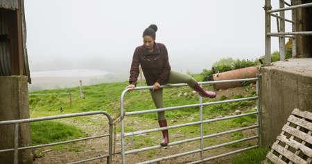 Beautiful woman crossing gate in field