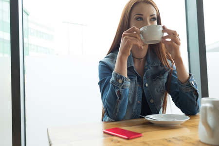 Woman looking away while having coffee at table in cafe