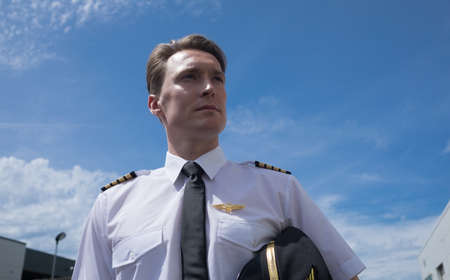 pilotos aviadores: Low angle view of confident young male pilot standing against blue sky on sunny day