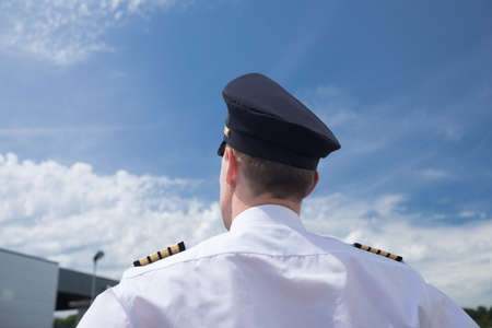 aviators: Rear view of male pilot standing against blue sky at airport on sunny day
