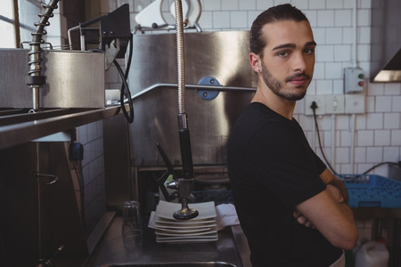 sink: Portrait of young waiter standing in kitchen at cafe