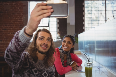 Young man with friend taking selfie at counter in cafe