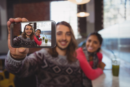 Happy young man with friend taking selfie at counter in cafe