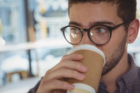 Close-up of man looking away while drinking coffee Stock Photo