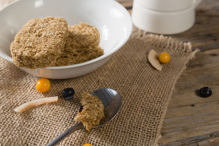 Close-up of granola bar and berry fruit on wooden table Stock Photo