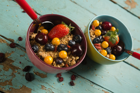 Bowls of breakfast cereals and fruits with spoon on wooden table Stock Photo