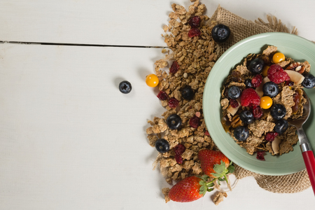Bowl of breakfast cereals and fruits with spoon on wooden table Stock Photo