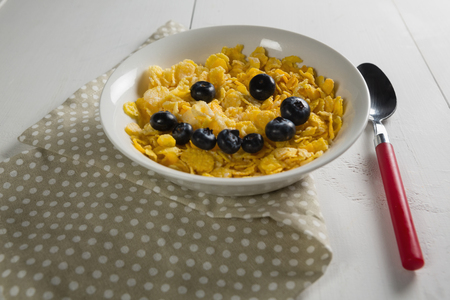 Wheaties cereal and blueberry in bowl with table cloth and spoon on white background