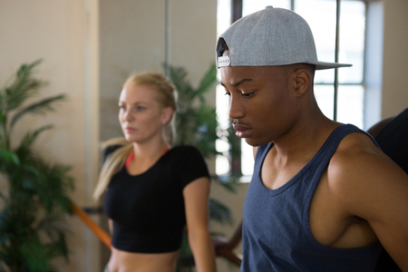 woman mirror: Thoughtful male dancer with friend by mirror in studio Stock Photo