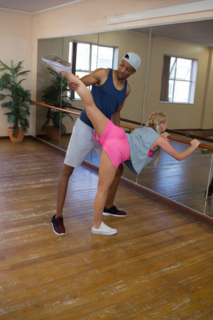woman mirror: Full length of man assisting female dancer in stretching leg on barre at studio