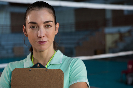 Portrait of confident female volleyball coach with clipboard at court