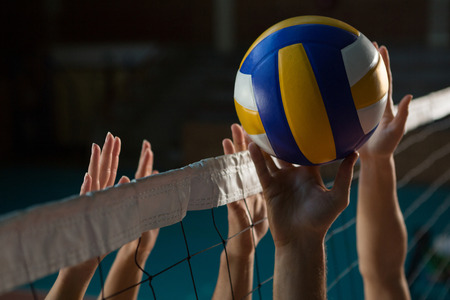 Bebouwde handen van spelers die volleyballen aan het hof