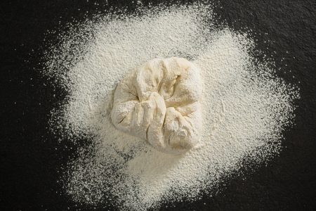 Overhead view of flour on dough at table