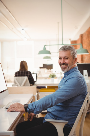 Portrait of smiling male executive sitting at desk in office