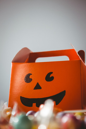 Low angle view of orange box with anthropomorphic smiley face against white background