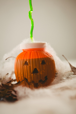 Close up of drink in jack o lantern container over white background