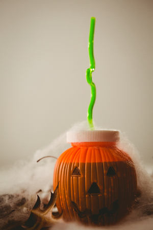 Close up of drink in jack o lantern container against white background Imagens