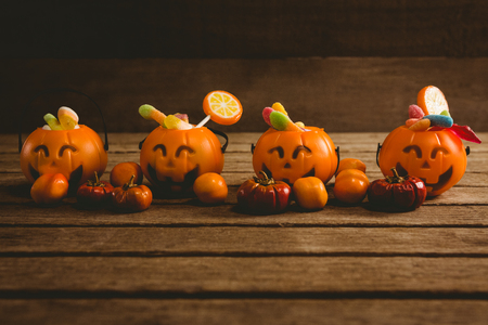 Jack o lantern containers with food arranged on wooden table