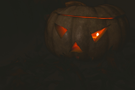 darkroom: Close up of white jack o lantern glowing in darkroom during Halloween Stock Photo