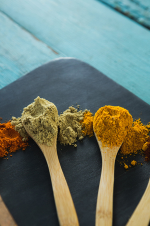 Close-up of various spice powder in wooden spoon Stock Photo