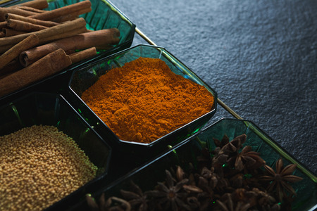 Close-up of anise and cinnamon with spices powder in tray Stock Photo