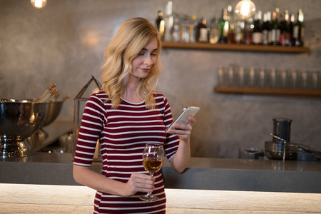counter top: Beautiful woman using mobile phone while having wine in restaurant Stock Photo