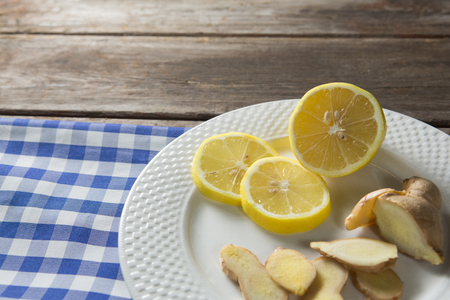 Close up of lemon and ginger slices in plate with napkin on table