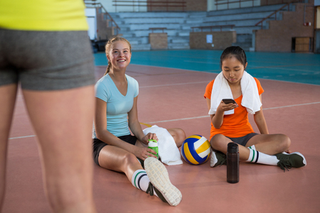 Smiling female players having a break in the volleyball court