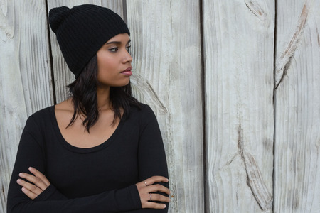 contemplated: Thoughtful young woman standing with arms crossed against wooden wall Stock Photo