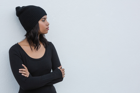 contemplated: Thoughtful young woman standing with arms crossed against white wall Stock Photo
