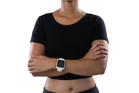athletic wear: Mid section of female athlete standing with arms crossed against white background Stock Photo