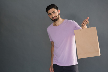 Portrait of man holding shopping bag against grey background