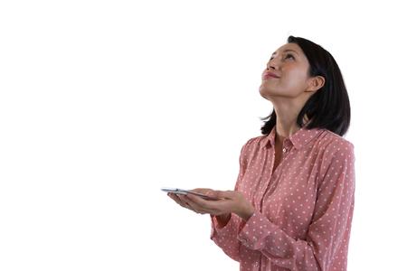 Female executive holding mobile phone against white background Stock Photo