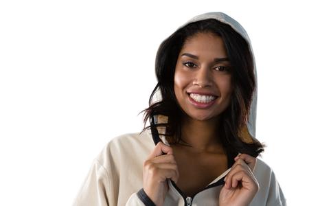 Close up portrait of smiling female athlete wearing hooded jacket against white background
