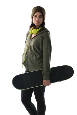 Confident young woman carrying skateboard against white background