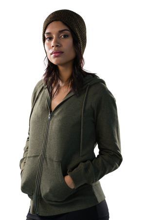 Portrait of young woman in hooded jacket standing against white background