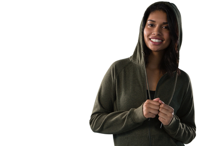 Portrait of smiling female athlete in hooded jacket against white background