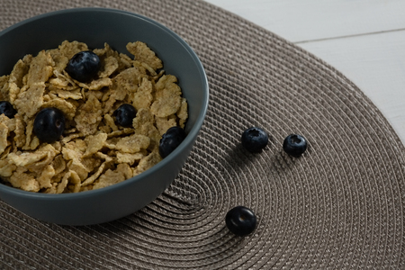Bowl of wheat flakes and blueberry on placemat