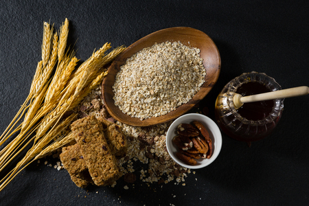 Breakfast cereal with barley, honey and granola bar on black background