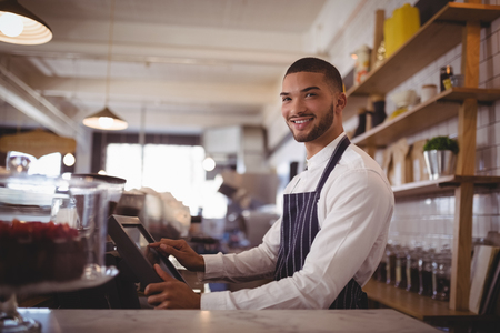 Smiling handsome young waiter using computer at counter in coffee shop