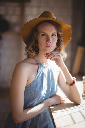 Portrait of beautiful young woman wearing hat standing by table at coffee shop