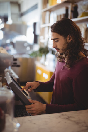 Side view of young waiter with long hair using cash register at counter in coffee shop Reklamní fotografie - 85776998
