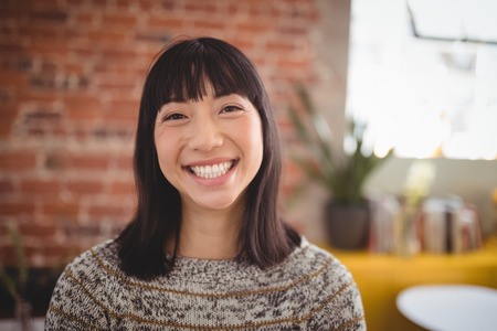 Close up portrait of smiling attractive young woman standing against brick wall at coffee shop Stock Photo