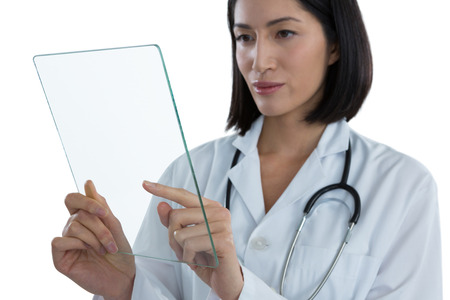 Female doctor using a glass digital tablet against white background