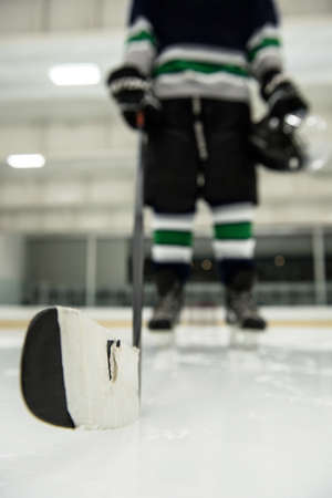 Low section of male player holding ice hockey stick at rink