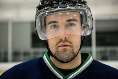 Close-up portrait of male ice hockey player wearing headwear at rink