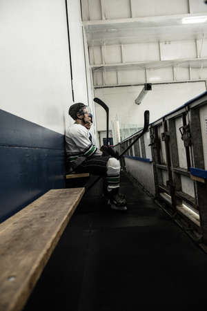 Male ice hockey player with teammate relaxing on seat at corridor