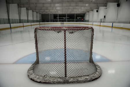 Goal post at empty illuminated ice hockey rink